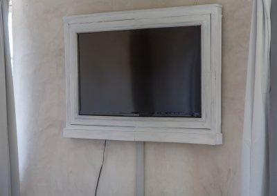 La télévision du mas d'élise est placée dans un cadre en bois pour s'intégrer à la décoration